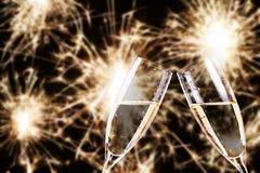 aclamaciones vidrios del champán con los fuegos artificiales en fondo Foto de archivo libre de regalías