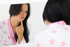 Acne. A young teen girl checking her acne in the bathroom mirror royalty free stock images