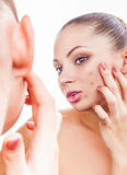 Acne in women. A young woman in a mirror treats acne on his face on a white background stock images