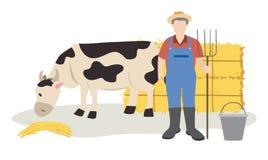 Acobarde comer o feno e o fazendeiro que estão com o forcado perto dos pacotes de feno Foto de Stock