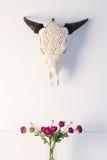 Acobarde el ornamento principal del cráneo de los toros con el interior casero de la decoración de las rosas rosadas foto de archivo libre de regalías