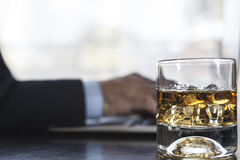 Acohol And Work. Man working on laptop with a glass of alcohol near him stock images
