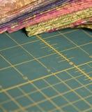 Acolche la estera rotatoria del corte con la tela en fondo fotos de archivo