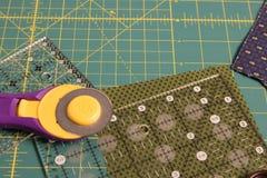 Acolche la estera rotatoria del corte con la tela en fondo Imagen de archivo
