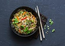 Acolchoe macarronetes tailandeses do udon dos vegetais do vegetariano em um fundo escuro, vista superior Alimento do vegetariano  imagens de stock