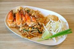 Acolchoe o estilo tailandês ou tailandês Fried Noodle Topped com os camarões de rio servidos na tabela de madeira fotografia de stock royalty free