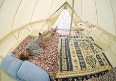 Acomodação exterior de Glamping Homens do turista com o smartphone que encontra-se na cama dentro da barraca de acampamento com i fotografia de stock royalty free
