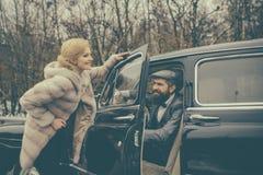 Acompañamiento de muchacha por seguridad Hombre barbudo y mujer atractiva en abrigo de pieles Pares en amor fecha romántica Colec foto de archivo