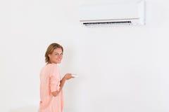 Acondicionador de aire de funcionamiento de la mujer foto de archivo