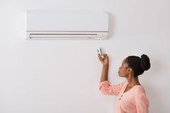 Acondicionador de aire de funcionamiento de la mujer con teledirigido Fotografía de archivo libre de regalías