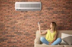 Acondicionador de aire de funcionamiento de la mujer mientras que se sienta en el sofá en casa imagenes de archivo