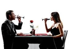 Acopla os amantes que bebem silhuetas do jantar do vinho foto de stock