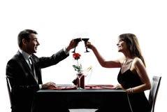 Acopla os amantes que bebem silhuetas do jantar do vinho imagem de stock