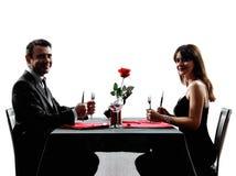 Acopla os amantes que datam o jantar silhuetas com fome Foto de Stock