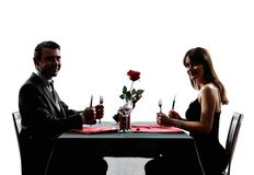 Acopla os amantes que datam o jantar silhuetas com fome Imagens de Stock