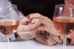 acoplamento O homem põe um anel de diamante sobre o dedo de uma mulher Os vidros de vinho estão estando ao lado de imagens de stock royalty free