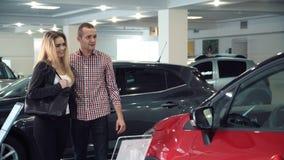 Acople a admiração de um carro vermelho em uma sala de exposições Fotos de Stock