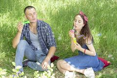 Acople amantes fundem bolhas os amigos riem o menino e a menina do piquenique do verão estão sentando-se na grama imagens de stock