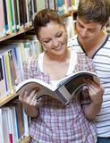 Acople a apreciação lendo um livro na biblioteca Imagem de Stock