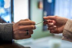 Acople as mãos que dão o cartão de crédito, na verificação geral Imagem de Stock Royalty Free