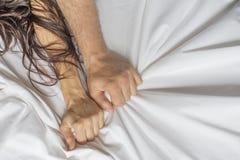Acople as mãos que puxam as folhas brancas na êxtase, orgasmo Conceito da paixão Oorgasm Momentos eróticos conceito íntimo sexo fotografia de stock royalty free