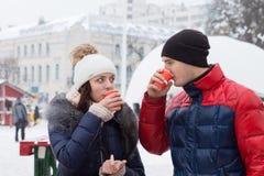 Acople bebidas quentes sorvendo em uma praça da cidade invernal Foto de Stock Royalty Free