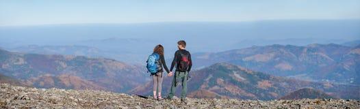 Acople caminhantes com as trouxas no cume da montanha Fotografia de Stock Royalty Free