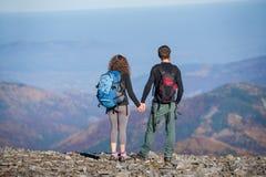 Acople caminhantes com as trouxas no cume da montanha Fotografia de Stock