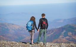 Acople caminhantes com as trouxas no cume da montanha Fotos de Stock Royalty Free