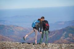Acople caminhantes com as trouxas no cume da montanha Imagem de Stock