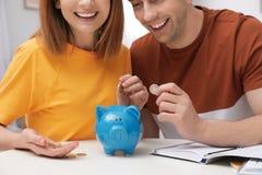 Acople a colocação de moedas no mealheiro na tabela Dinheiro da economia imagem de stock royalty free