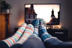 Acople com as peúgas e as meias de lã que olham filmes ou séries na tevê no inverno Mulher e homem que sentam-se ou que encontram fotos de stock