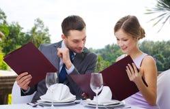 Acople com menus no restaurante fotos de stock royalty free