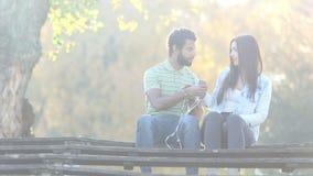 Acople começar escutar a música no smartphone, compartilhando de fones de ouvido video estoque