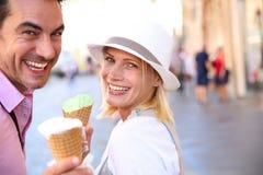 Acople comer o gelado na rua no dia ensolarado fotografia de stock