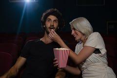 Acople comer a pipoca ao olhar o filme no teatro foto de stock