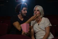 Acople comer a pipoca ao olhar o filme no teatro imagens de stock