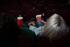 Acople comer a pipoca ao olhar o filme no teatro imagens de stock royalty free