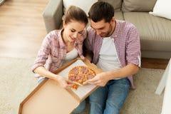 Acople comer a pizza afastada em casa imagem de stock royalty free
