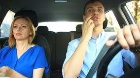 Acople a condução no carro, em um homem e em um passeio da mulher junto no carro através das ruas da cidade e do olhar ao redor video estoque