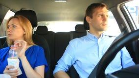 Acople a condução no carro, em um homem e em um passeio da mulher junto no carro através das ruas da cidade e do olhar ao redor vídeos de arquivo