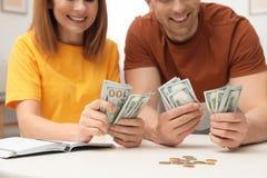Acople a contagem do dinheiro na tabela dentro fotografia de stock royalty free