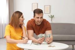 Acople a contagem do dinheiro na tabela dentro fotos de stock royalty free