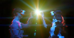 Acople dos povos comunicam-se usando uns auriculares da realidade virtual Imagem com efeito do pulso aleat?rio fotos de stock