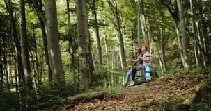 Acople dos turistas que descansam com chá na floresta video estoque
