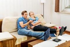 Acople em casa, homem que olha o sono da mulher da tevê Fotos de Stock