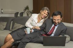 Acople em casa no formalware com funcionamento do homem e observação da mulher fotos de stock