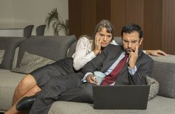 Acople em casa no formalware com funcionamento do homem e observação da mulher imagens de stock royalty free