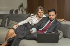 Acople em casa no formalware com funcionamento do homem e observação da mulher fotos de stock royalty free