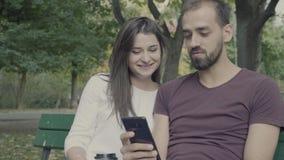 Acople em um banco no parque que olha o smartphone vídeos de arquivo